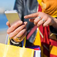 Woman viewing shopping options on her cell phone