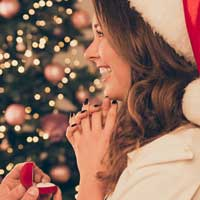 Man proposes to a woman with a ring in a red velvet box near a Christmas tree