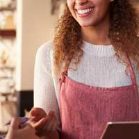 Cashier laughs with costumers during purchase process