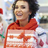 Young woman in a Christmas sweater holding a wrapped present while holiday shopping